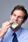 Businessman stuffing money in his mouth. Royalty Free Stock Photos