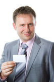 Businessman in stylish suit holding business card. Portrait of a handsome young business man in a stylish suit holding a blank business card, place to record Royalty Free Stock Photo