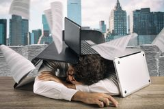 Tired businessman sleeping under a pile of laptops due to workload. Businessman submerged by work and papers in the office stock images
