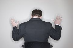Businessman Submission. Businessman submits while he is sitting in his office chair in his office stock photography