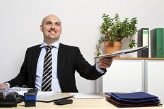 Businessman submits smilingly a folder Stock Images