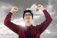 Businessman succeed. Young businessman raised his hands in victory under cloudy sky Stock Photography