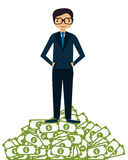 Businessman succeeded. A man in a suit standing on a mountain of money. Business concept Stock Photos