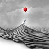 Businessman Success Concept. As a metaphor to overcome obstacles as a person lifting a maze or labyrinth using a red balloon as a symbol for vision and finding Royalty Free Stock Photos