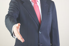 Businessman. Successful business man offering his hand on a white background Royalty Free Stock Photography