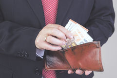 Businessman. Successful businessman taking money out of your wallet Royalty Free Stock Photos