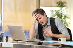 Businessman suffering an anxiety attack. With the hands in his chest and head sitting in a desktop at office royalty free stock photography