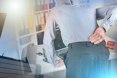 Businessman suffering from back pain, light effect; multiple exp. Businessman suffering from back pain in office, light effect; multiple exposure stock photos