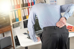 Businessman suffering from back pain, light effect. Businessman suffering from back pain in office, light effect Stock Photo