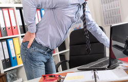 Businessman suffering from back pain. In office Royalty Free Stock Images