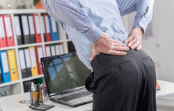 Businessman suffering from back pain. In office Stock Photos