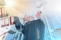 Businessman suffering from back pain; multiple exposure. Businessman suffering from back pain at office; multiple exposure royalty free stock image