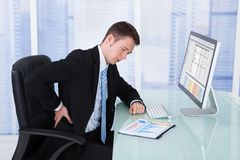 Businessman suffering from backache at computer desk. Young businessman suffering from backache at computer desk in office Stock Photo
