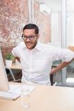 Businessman suffering from backache at desk. Young businessman suffering from backache at office desk stock photo