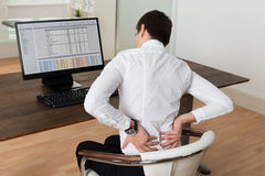 Businessman Suffering From Backache At Desk Royalty Free Stock Images