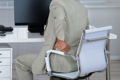 Businessman Suffering From Backache While Sitting On Chair Stock Image