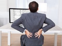 Businessman suffering from backache while sitting at desk Royalty Free Stock Image