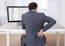 Businessman suffering from backache while sitting at desk Royalty Free Stock Photography