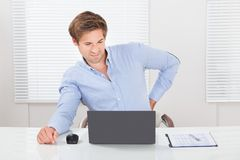 Businessman suffering from backache while working on laptop. Tired businessman suffering from backache while working on laptop desk in office Royalty Free Stock Image