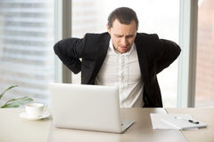 Businessman suffering from backache at workplace. Man feels strong lower back pain after long hours work in office. Businessman suffering from backache at Royalty Free Stock Image