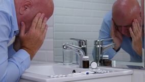 Businessman suffering a big headache in bathroom with head in his hands.  stock footage