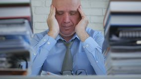 Businessman Suffering a Big Headache in Office Room royalty free stock image