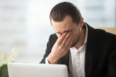 Businessman suffering from eyes fatigue at work. Frustrated businessman feels pain in eyes because of eyesight overstrain after long computer work. Tired young royalty free stock images