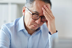 Businessman suffering from headache at office Stock Image