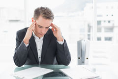 Businessman suffering from headache at office desk Royalty Free Stock Photo