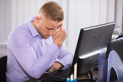 Businessman Suffering From Headache. Sitting In Front Of Computer Stock Photo