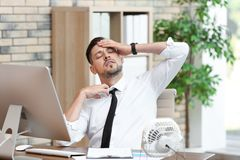 Businessman suffering from heat in front of small fan. At workplace royalty free stock images