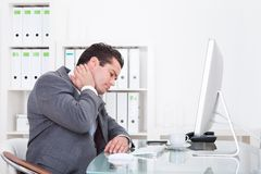Businessman suffering from neck pain. Young Businessman In Office At Desk Suffering From Neck Pain Stock Images