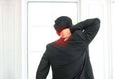 Businessman suffering from shoulder pain in office Stock Photos