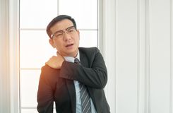 Businessman suffering from shoulder pain in office Stock Image