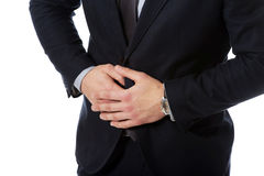 Businessman suffering from stomach pain. Young handsome businessman suffering from stomach pain Stock Photos