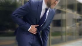 Businessman suffers from sharp stomach ache, gastritis, heartburn, dizzy effect