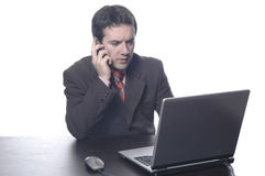 Businessman in a suit behind a. The businessman in a suit behind a table, with portable PC Stock Photo