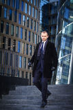 Businessman in suit and coat walking outdoors office. Businessman walking outdoors in front of a modern office building Royalty Free Stock Photo