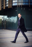 Businessman in suit and coat walking outdoors office. Businessman walking outdoors in front of a modern office building Stock Images