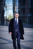 Businessman in suit and coat walking outdoors office. Businessman walking outdoors in front of a modern office building Royalty Free Stock Images