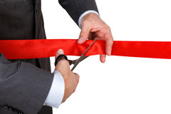 Businessman in suit cutting red ribbon with pair of scissors iso Royalty Free Stock Images