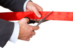 Businessman in suit cutting red ribbon with pair of scissors iso Stock Photo
