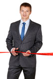 Businessman in suit cutting red ribbon with pair of scissors iso Stock Photography