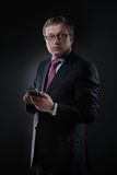 Businessman in a suit on a dark background Stock Photos