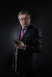 Businessman in a suit on a dark background Stock Image