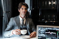 Businessman in suit drinking coffee while sitting in a restaurant. Handsome businessman in suit drinking coffee while sitting in a restaurant with laptop Stock Images