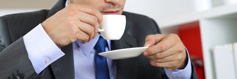 Businessman in suit drinking hot fresh morning cup of coffee Stock Photos