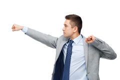 Businessman in suit fighting with someone. Business, people and conflict concept - businessman in suit fighting with someone imaginary stock photo