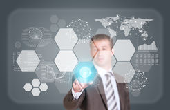 Businessman in suit finger presses virtual button. Graphs, world map, network and other elements as backdrop Stock Image