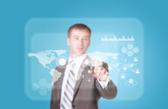 Businessman in suit finger presses virtual button. Transparent rectangles, world map, network as backdrop Stock Photos